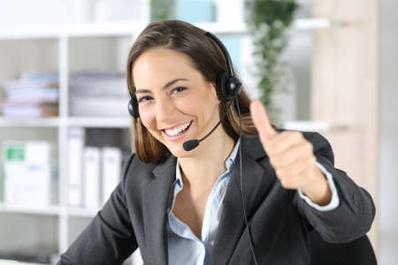 Happy telemarketer woman with thumbs up wearing headset looking at camera sitting at the office Archivio Fotografico