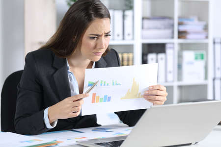 Sad executive woman showing bad results graph report on videocall on aptop sitting on her desk at office