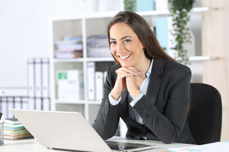 Happy executive woman posing looking at camera sitting on a desk at the office
