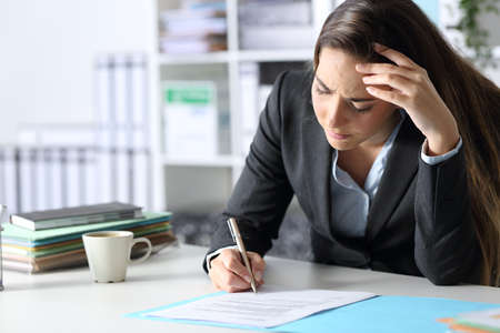 Worried executive woman signing contract sitting on a desk at the office
