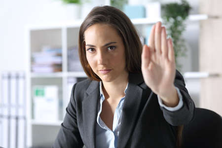 Serious executive woman looking at camera gesturing stop sitting at the office