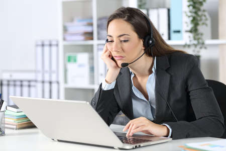 Bored telemarketer woman with laptop sitting on a desk at the office Archivio Fotografico