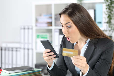 Surprised executive woman paying on smart phone with credit card sitting on a desk at the office Archivio Fotografico