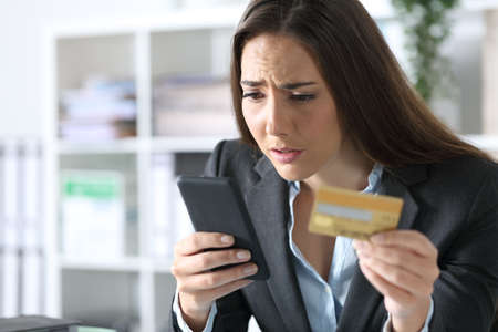 Worried executive woman paying on smart phone with credit card sitting at the office Archivio Fotografico