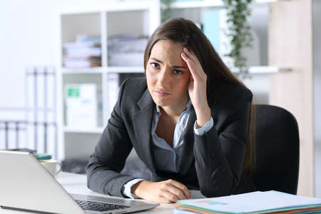 Sad executive woman compaining looking at camera sitting on her desk at office
