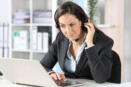 Suspicious telemarketer woman with headset looking at laptop sitting on a desk in the office