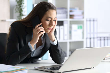 Bored executive with laptop waiting calling on smart phone sitting on her desk at office
