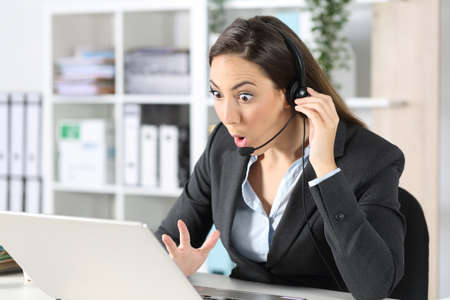 Surprised telemarketer woman with headset reading good news on laptop sitting on a desk at office