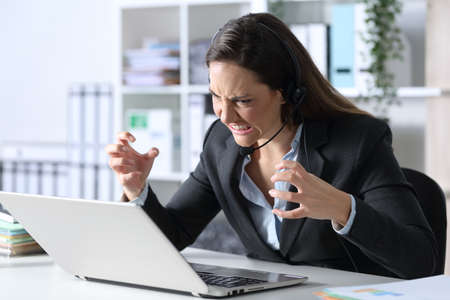 Angry telemarketer woman looking at laptop sitting on a desk at the office