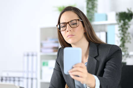 Executive woman wearing eyeglasses with eyesight problem trying to read on smart phone sitting on her desk at office
