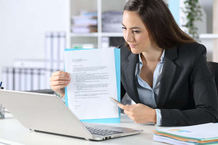Executive woman showing contract on videocall on laptop sitting on her desk at office Foto de archivo