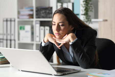 Bored executive woman looking at laptop sitting on her desk at the office Imagens