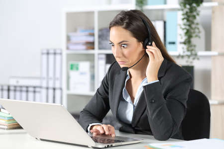 Confused telemarketer woman looking at laptop sitting on a desk at the office