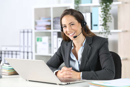 Happy telemarketer woman with headset and laptop posing looking at camera sitting on a desk at the office Фото со стока