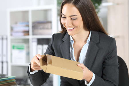 Happy executive woman opening package delivery sitting on a desk at the office