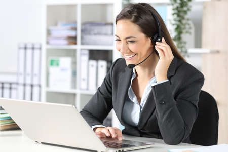 Happy telemarketer woman with laptop attending call with headset sitting on a desk at the office