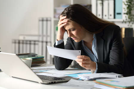 Sad executive woman complaining holding receipt sitting on her desk at night at office