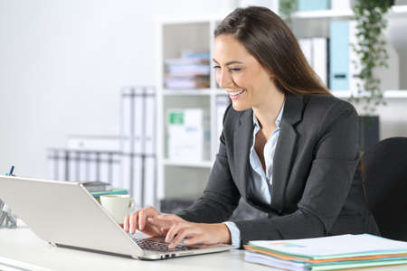 Happy executive woman typing on laptop sitting on a desk at the office Archivio Fotografico