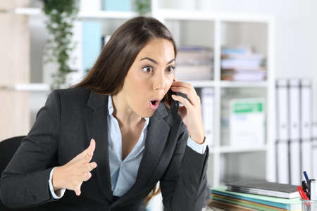 Surprised executive woman calling on smart phone sitting on a desk at the office