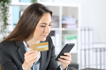 Executive woman paying online on smart phone with credit card sitting on a desk at office
