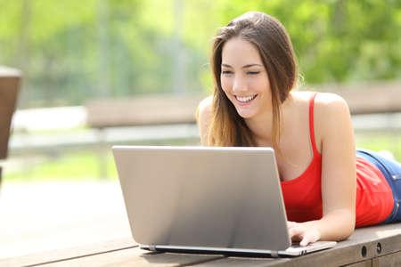 Glückliche Frau in Rot mit Laptop, die im Sommer auf einer Parkbank liegt