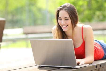 Happy woman in red with laptop lying on a park bench in summer