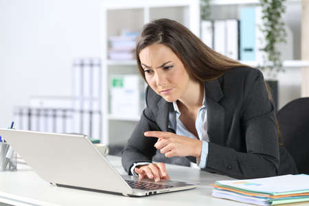 Suspicious executive woman reading and pointing on laptop sitting on a desk at the office
