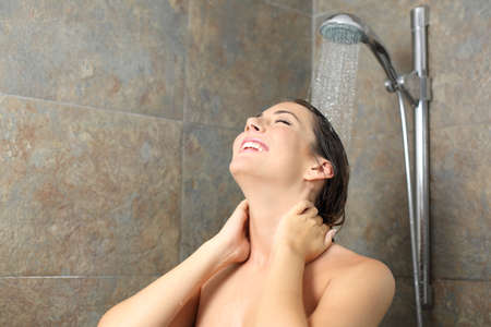 Happy woman relaxing having a shower standing with water falling on head on a bathroom