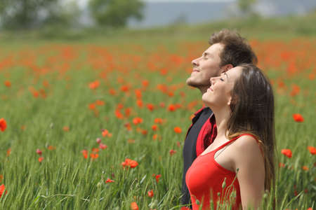Happy couple breathing fresh air standing between the grass on a green poppy field