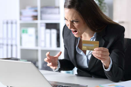 Angry executive woman pays online with credit card on laptop sitting on a desk at the office