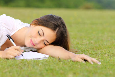 Happy woman writing on notebook with marker lying on green grass on a park in summer