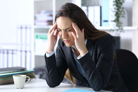 Sick executive with migraine complaining in pain rubbing temples sitting on a desk at office
