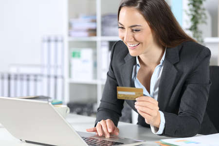Happy executive woman pays online with credit card on laptop sitting on a desk at office