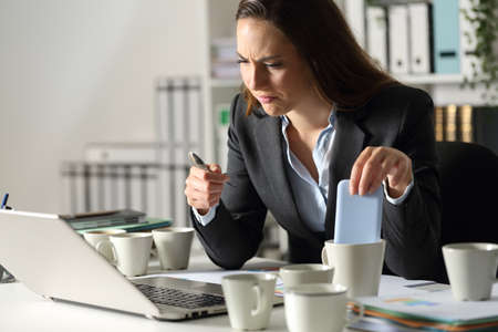 Overworked executive woman makes mistakes due to exhaustion with several coffee cups sitting in the night at office