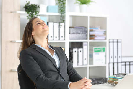 Happy executive woman breathing fresh air sitting on a desk at the office Archivio Fotografico