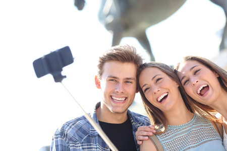 Happy friends smiling taking selfie on smart phone with stick outdoors on vacation