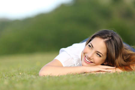Happy woman thinking lying on green grass looking sideways on a park at summer Archivio Fotografico