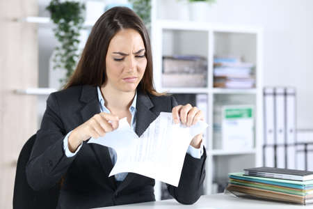 Angry executive woman ripping contract sitting on a desk at the office