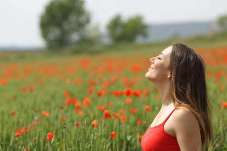 Profile of a satisfied woman breathing fresh air on a green poppy field in spring