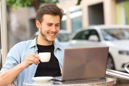 Happy man reading on laptop holding cup sitting on a coffee shop terrace
