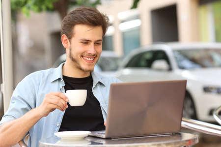 Glücklicher Mann, der auf einem Laptop liest, der eine Tasse hält, die auf einer Café-Terrasse sitzt?
