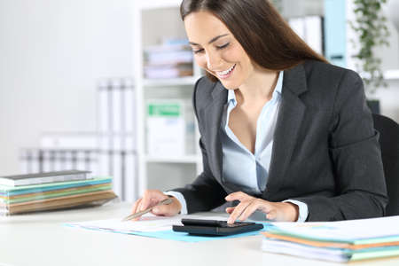 Happy bookkeeper woman calculating on calculator checks document sitting on a desk at the office