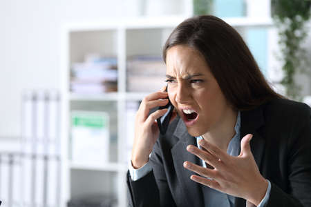 Angry executive woman arguing calling on smart phone sitting on a desk at the office