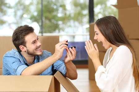 Happy man proposing to excited girlfriend with wedding ring while moving at new home surrounded by boxes Imagens