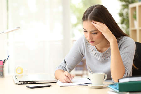 Concentrated woman writing notes on notebook sitting on a desk at home