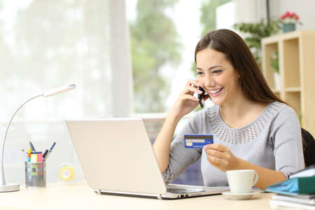 Happy woman with laptop talking on smart phone holding credit card sitting on a desk at home Фото со стока