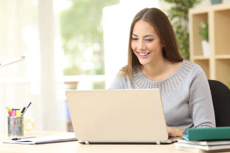 Happy student girl using laptop sitting on a desk in the living room at home Stock Photo