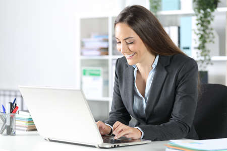 Happy executive woman typing on laptop sitting on a desk at the office