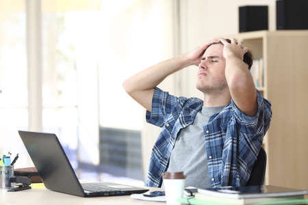 Sad student man with laptop complaining sitting on a desk at the office Stock Photo