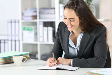 Happy executive woman writing notes on agenda sitting on a desk at the office